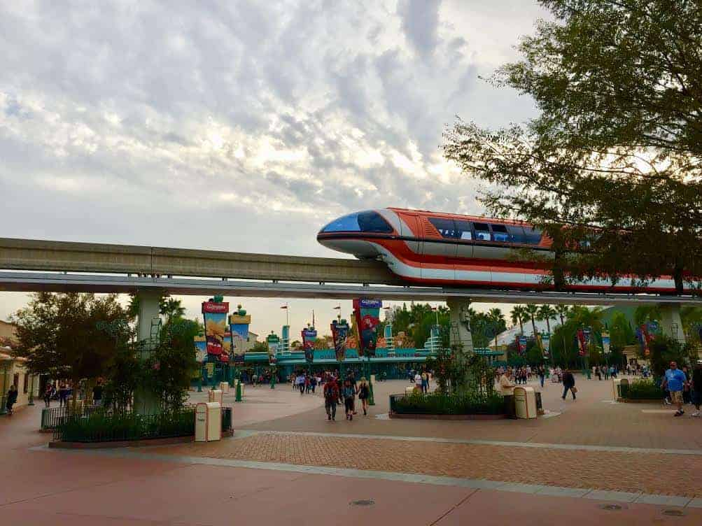 Disneyland Monorail glides across the esplanade at Disneyland Resort, with California Adventure entrance in the background.