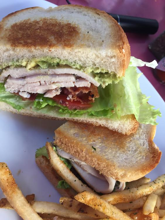Carnation Turkey club sandwich cut in half with seasoned fries.